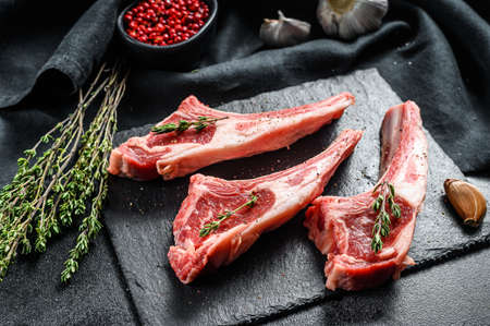Raw lamb chops, Rack of Lamb with rosemary and spices. Organic meat steak. Black background. Top view. Archivio Fotografico