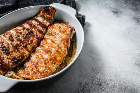 Spicy hot grilled pork spare ribs from BBQ served in a pan. Gray background. Top view. Copy space.