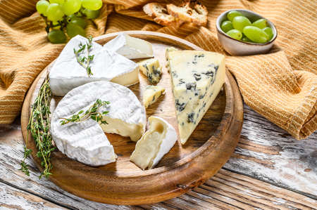 Cheese plate with Camembert, brie and blue cheese with grapes. White wooden background. Top view 写真素材
