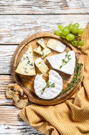 Cheese plate with Camembert, brie and blue cheese with grapes. White wooden background. Top view.