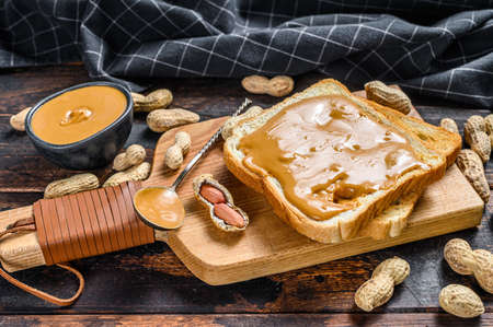 Crispy toast with peanut butter on breakfast. Dark Wooden background. Top view.