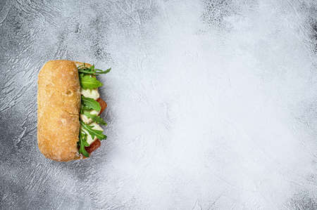 Sandwich with fresh Camembert cheese, pear marmalade, ricotta and arugula. Gray background. Top view. Space for text.