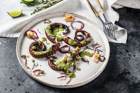 Cooked octopus tentacles with pesto, thyme and onion. Black background. Top view.