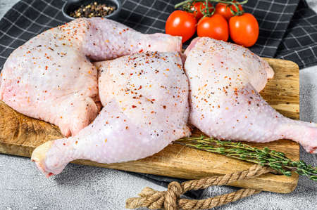 Fresh raw chicken thighs, legs on a cutting Board with spices, cooking. Gray background. Top view. Copy space.