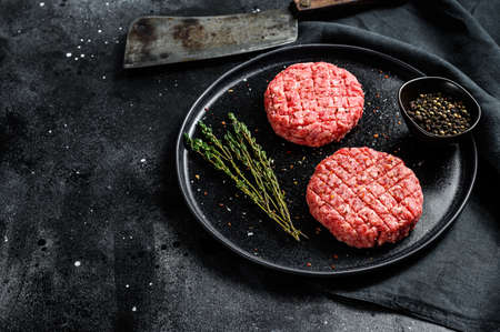 Raw burgers cutlets, organic ground beef meat. Black background. Top view. Copy space
