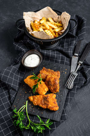 Pan fried cod fillet and French fries. Black background. Top view.