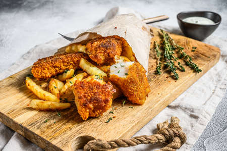 Fish and chips, French fries and cod fillet fried in breadcrumbs. Gray background. Top view.