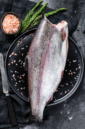 Fresh trout fish with salt and rosemary. Black background. Top view.