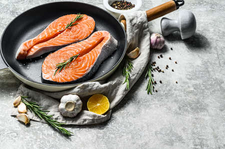 Raw salmon steak in a frying pan. Healthy seafood. Gray background. Top view. Space for text