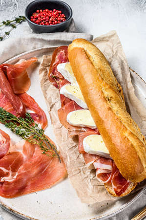 Baguette sandwich with prosciutto ham, Camembert cheese on a plate. Gray background, top view