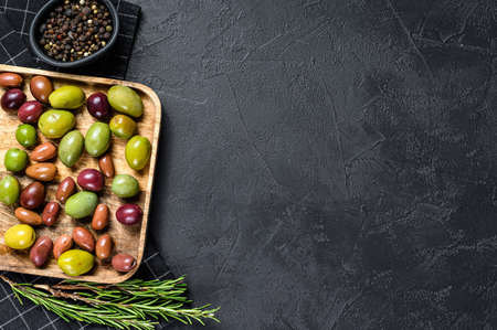 Mix of colorful salted olives with a bone. Black background. Top view. Space for text.