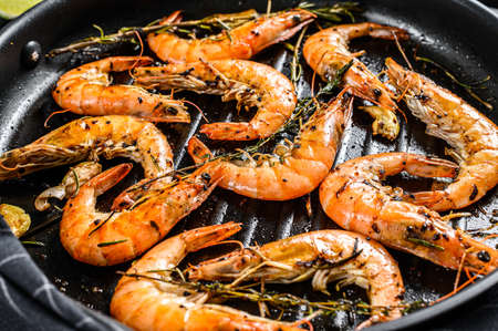 Grilled giant langoustine shrimps, prawns in a frying pan. Black background. Top view Archivio Fotografico