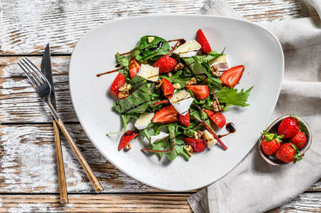 Salad with Camembert, strawberries, nuts, chard and arugula. White background. Top view.