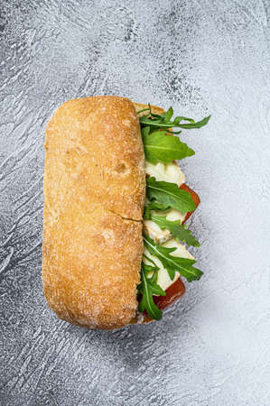 Sandwich with fresh Camembert cheese, pear marmalade, ricotta and arugula. Gray background. Top view.