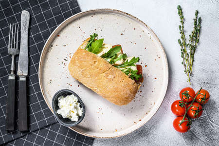 Ciabatta sandwich with fresh goat cheese, pear marmalade and arugula. Gray background. Top view. 写真素材