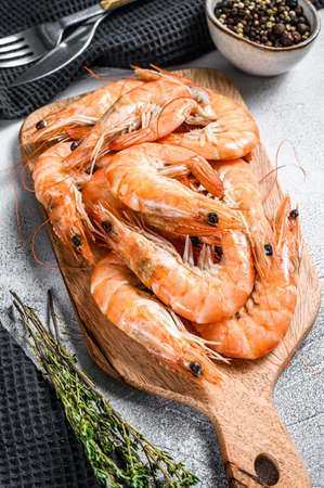 Fresh king shrimps, prawns on a wooden chopping Board. White background. Top view. Stok Fotoğraf