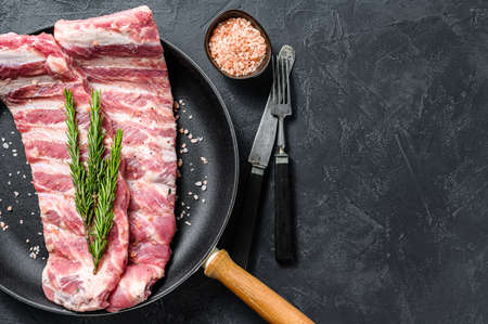 Rack of uncooked raw pork spare ribs seasoned with spices in a pan. Black background. Top view. Copy space.