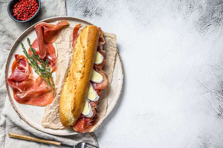 Baguette sandwich with prosciutto ham, Camembert cheese on a plate. Gray background, top view, space for text.