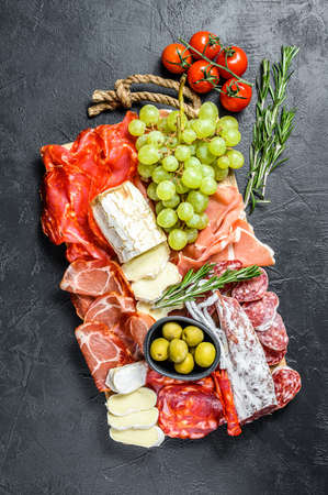 Italian antipasto, wooden cutting board with prosciutto, ham, parma, goat and Camembert cheese, olives, grapes. antipasti. Black background. Top view. 写真素材