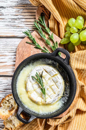 Baked brie cheese, Camembert with rosemary in a pan. White wooden background. Top view. 写真素材