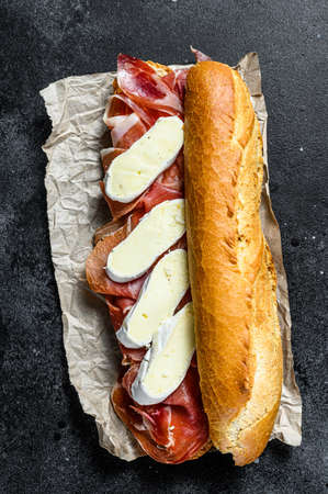 baguette sandwich with jamon ham serrano, paleta iberica, Camembert cheese. Black background, top view