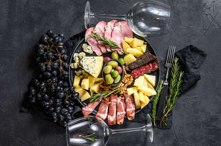 Antipasto board with sliced meat, ham, salami, cheese, olives. Black background. Top view. Reklamní fotografie