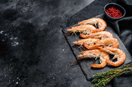 Raw fresh Prawns, shrimps Langostino on a stone Board. Black background. Top view. Copy space.