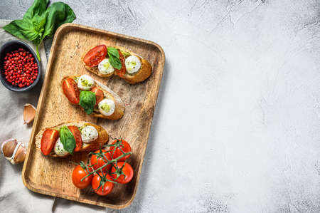 sandwiches with tomatoes, mozzarella cheese and basil. italian appetizer, antipasto. gray background. top view. Copy space.