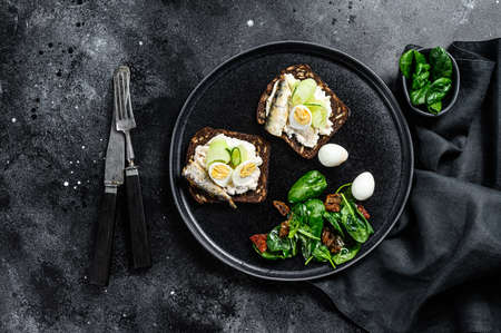 Sandwiches with sardines, egg, cucumber and cream cheese, salad garnish with spinach and dried tomatoes. Black background. Top view.