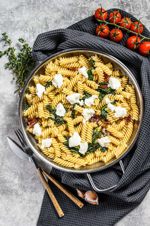 Delicious pasta fusilli dish with creamy spinach sauce and dried tomatoes. Gray background. Top view.