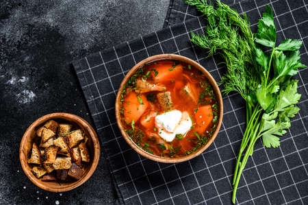 Russian speciality Borsch soup with beetrots and sour cream. Black background. Top view.