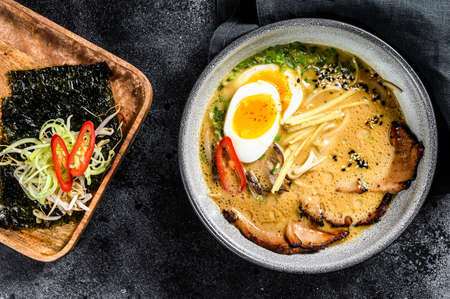 Ramen asian noodle soup with Beef tongue meat, mushroom and Ajitama pickled egg. Black background. Top view.