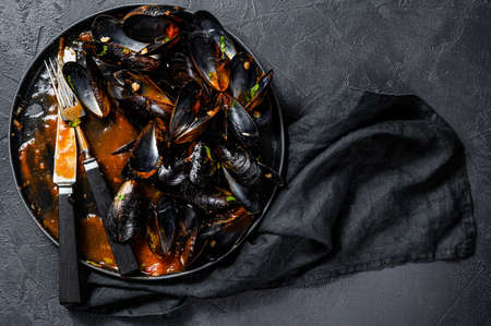 dirty plate with the remains of dinner, mussel shells. Black background. Top view.