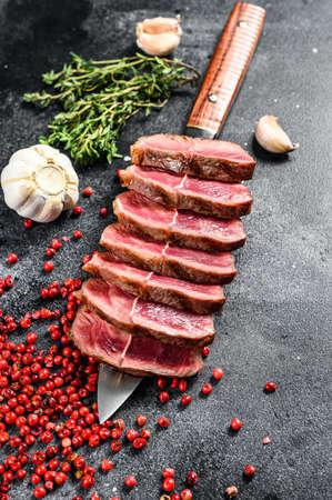 Sliced Grilled Top Blade steak. Organic beef meat. Black background. Top view.