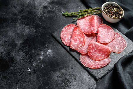 Spanish salami salchichon on a black chopping Board. Black background. Top view. Copy space. Zdjęcie Seryjne