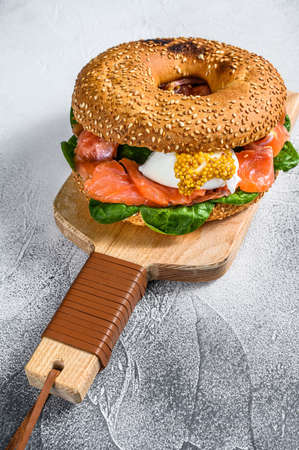 Bagel sandwich with salmon, cream cheese, spinach and egg. Gray background. Top view. Zdjęcie Seryjne