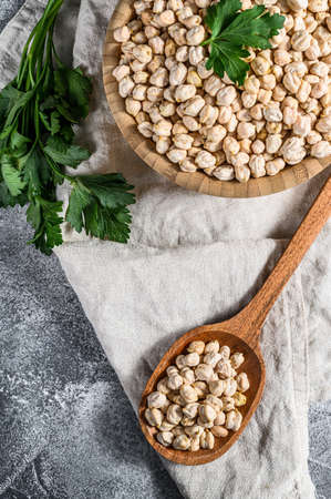 dried Chickpeas in a wooden spoon. Healthy vegetarian food. Gray background. Top view. Reklamní fotografie