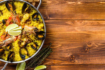 The Spanish paella with seafood prawns, shrimps, mussels in a paellera. Wooden background. Top view. Copy space. Stok Fotoğraf