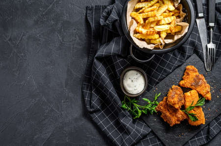 Fish and chips, traditional English food. Black background. Top view. Copy space.