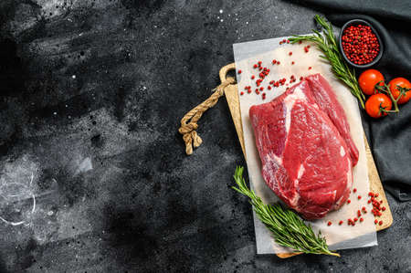 Raw brisket beef cut on a wooden cutting board. Black Angus beef. Black background. Top view. Copy space.