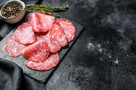 Salami sausage slices on a black chopping Board. Dark background. Top view. Copy space.