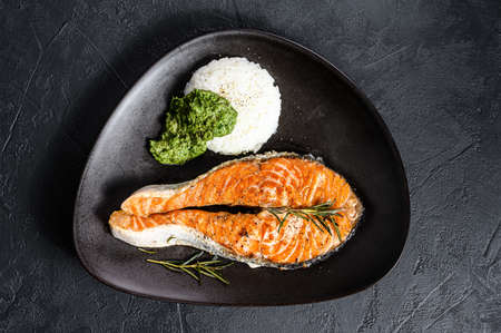 Grilled trout steak garnished with rice and spinach. Healthy seafood. Black background. Top view.