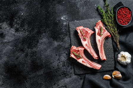 Raw lamb chops, Rack of Lamb with rosemary and spices. Organic meat steak. Black background. Top view. Copy space. Archivio Fotografico