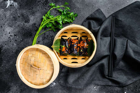 Black Dim sum dumplings in bamboo steamer. Asian cuisine. Black background. Top view. Zdjęcie Seryjne