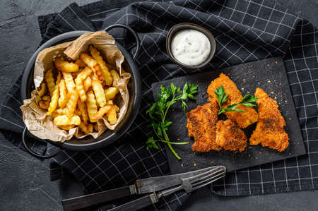 Fish and chips, French fries and cod fillet fried in breadcrumbs. Black background. Top view.