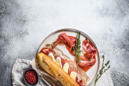 baguette sandwich with jamon ham serrano, paleta iberica, Camembert cheese on the cutting Board. Gray background, top view, space for text.