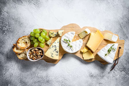 Assorted cheeses on a wooden cutting Board. Camembert, brie, Parmesan and blue cheese with grapes and walnuts. White background. Top view.