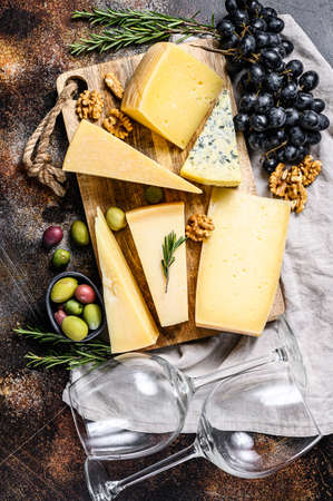 Collection of swiss, holland, french, italian cheeses with nuts and grapes. Dark background. Top view. 写真素材