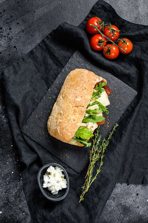 Ciabatta sandwich with fresh goat cheese, pear marmalade and arugula. Black background. Top view. 写真素材