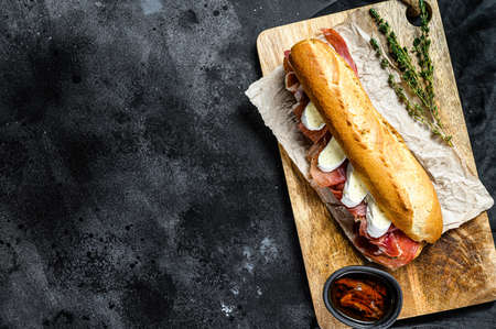 baguette sandwich with jamon ham serrano, paleta iberica, Camembert cheese on the cutting Board. Black background, top view, space for text.